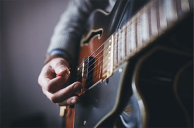 Photo: A musician strumming the strings of an electric guitar.